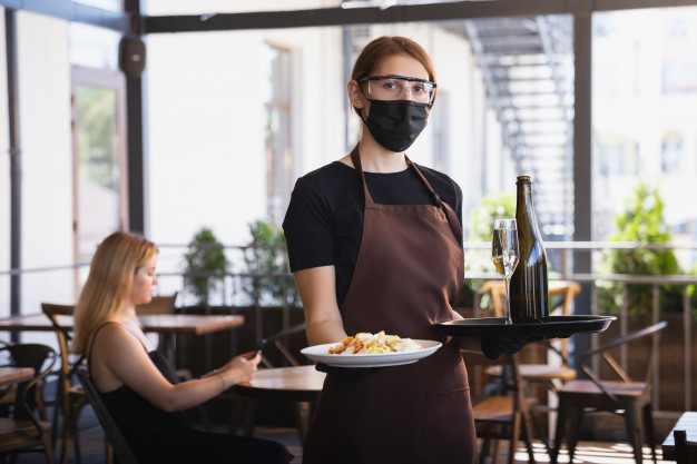 A waitress wearing a mask serving food in a restaurant.